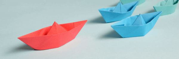 A metaphor for a leader in the form of a paper boat followed by little boats.